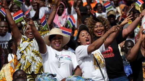 People waving The Gambian flag
