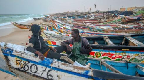 Two men sit together on one of many fishing boats painted in colourful motifs.