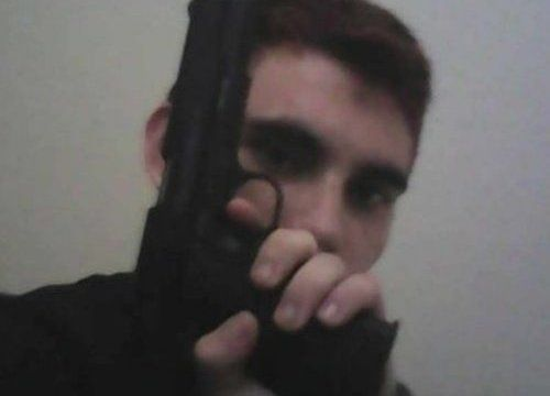 Nikolas Cruz, holding a gun in front of his face