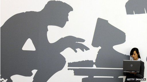 A woman using a laptop stands in front of a wall with a computer mural