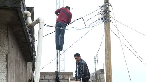 Villagers installing a new antenna