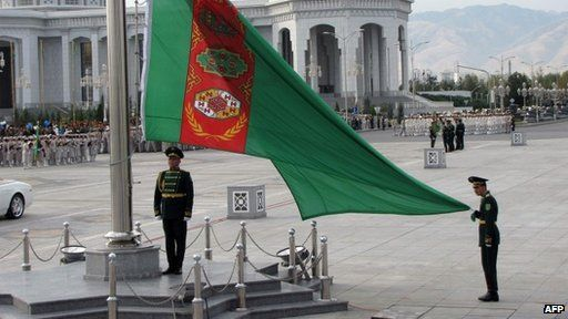 Soldiers raise the national flag during a military parade marking Turkmenistan's Independence Day (27 October 2013)