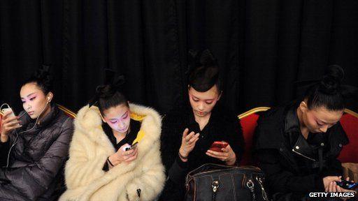 four women on their phones