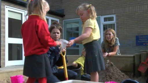 Nursery school children playing in sandpit