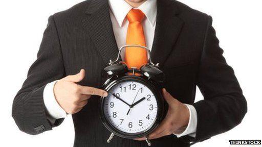 man holding a ticking clock
