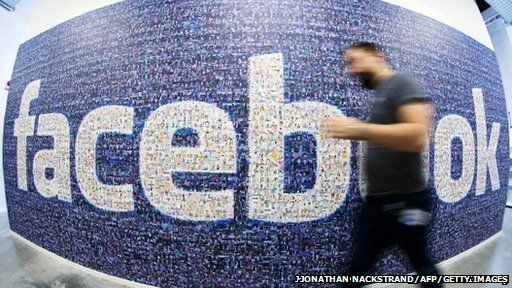 Man walking by a Facebook sign