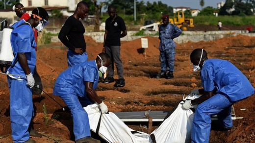 Health workers from the Sierra Leone's Red Cross Society Burial Team 7 place a body in a grave at King Tom cemetary in Freetown on November 12, 2014