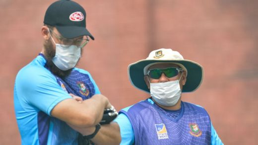 Bangladesh cricket team head coach Russell Domingo (R) and bowling coach Daniel Vettori wearing face masks watch the team during a practice session at Arun Jaitley Cricket Stadium in New Delhi on November 1, 2019,