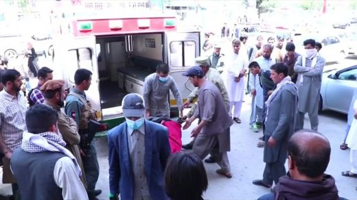 After the killing of journalist Mina Mangal, her body is transported in an ambulance