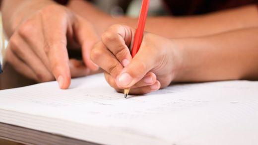 Mão de adulto aponta para caderno em que criança escreve com lápis