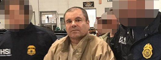 """This handout picture released by the Mexican interior ministry shows Joaquín """"El Chapo"""" Guzmán (centre) escorted by Mexican police officers before his extradition to the US. Photo: January 2017"""