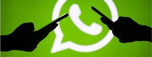 Two mobile phones and the WhatsApp logo