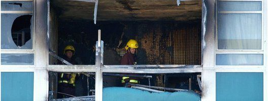 Two firemen check one of the burnt-out flats at Lakanal House