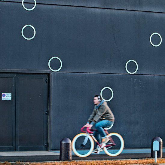 Man cycling past circles