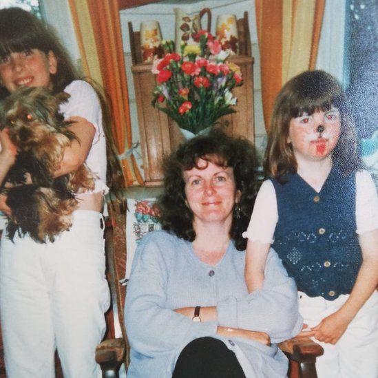 Y diweddar annwyl Sue Leighton, mam Philip, Lisa (sydd yn magu neu'n mogi'r ci!) a Catrin gyda'r gwyneb lliwgar.