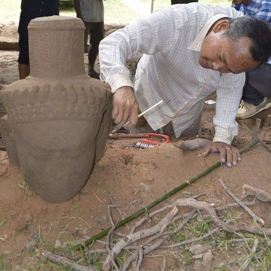 An archaeologist cleans the head of a statue after its excavation from the ground at the complex in Siem Reap province (01 August 2017)