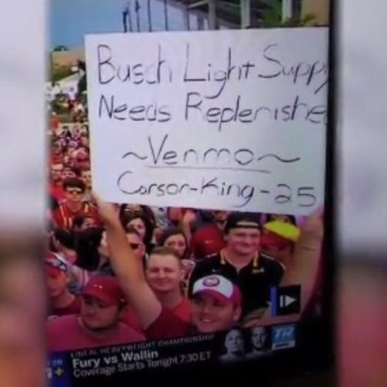 Mr Carson holding his sign on TV