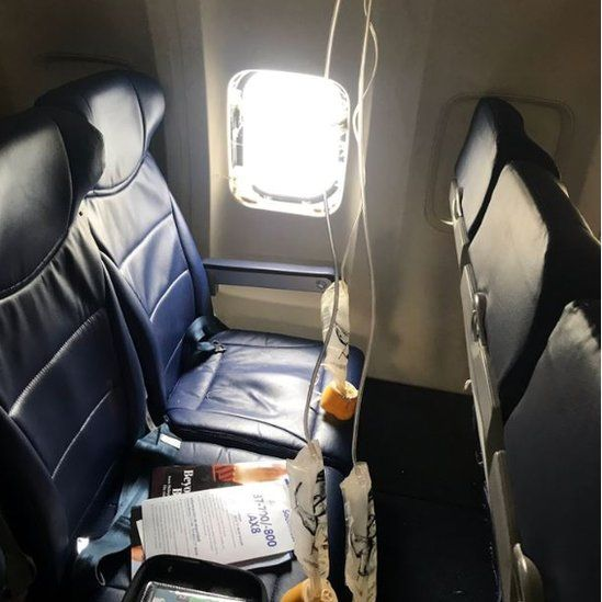 Passenger images shows a broken window and oxygen masks deployed