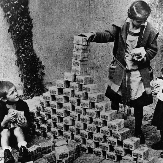 Children in Germany using mark notes to play of building a tower in 1923