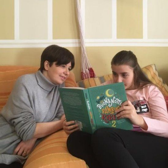 Daniela and her daughter Emma read together at home in Italy's red zone