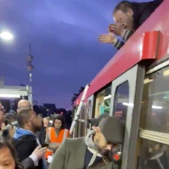 Protester speaking to commuters