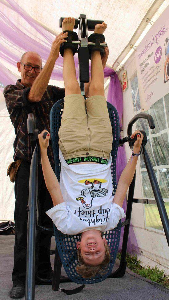A young festival-goer undergoes inversion therapy