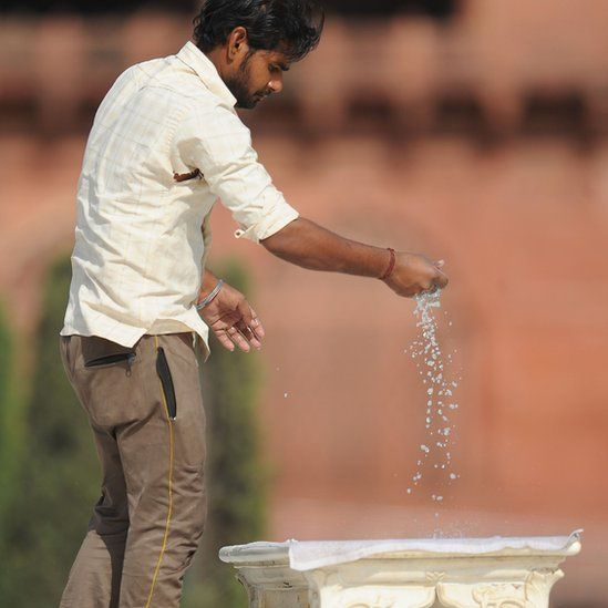 A man cleaning the iconic bench at the Taj Mahal