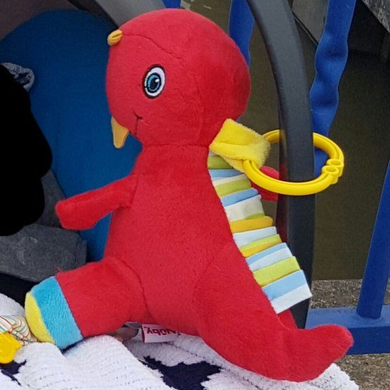 The red toy dinosaur that belonged to the baby
