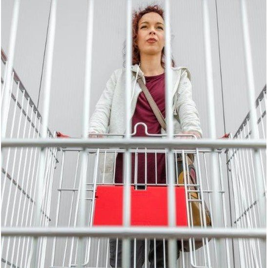 Woman looks through bars of empty shopping trolley