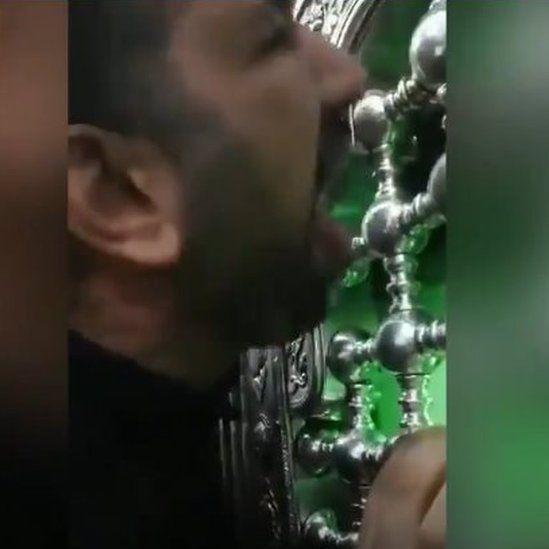 man licking holy shrine in Qom Iran