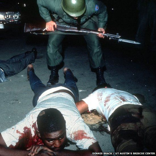 Wounded African American civilians on the ground, bloodied, while a policeman stands above them.