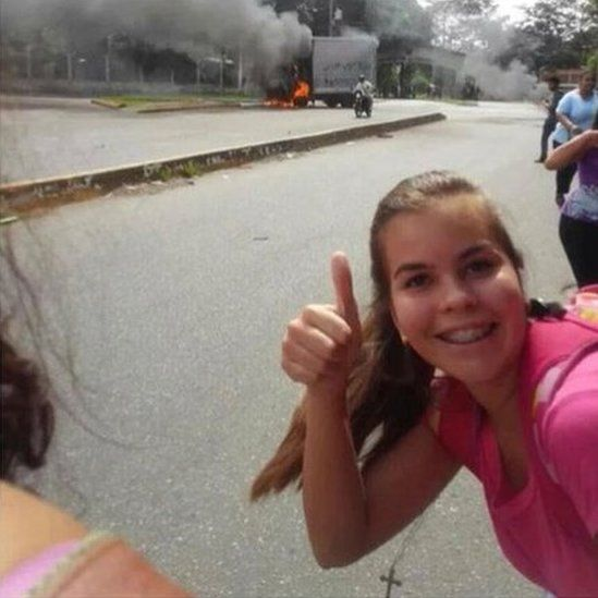 A girl is pictured doing a thumbs-up in front of a burning lorry.