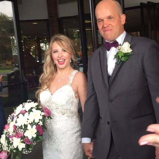 Heather and Christopher Dempsey smile for the cameras on their wedding day
