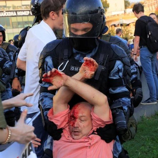 A bleeding rally participant is held by police in Moscow. Photo: 27 July 2019