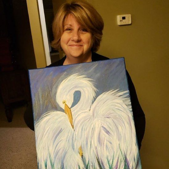 Cindi Decker with her painting of an egret