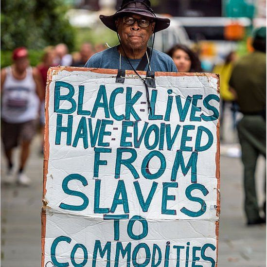 Activist holding sign reading BLACK LIVES HAVE EVOLVED FROM SLAVES TO COMMODITIES