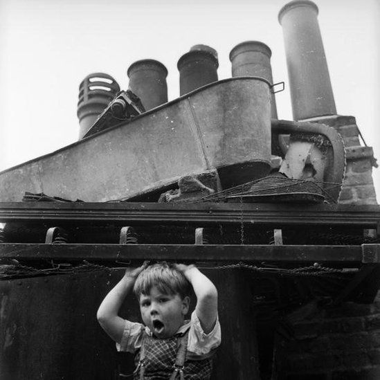 July 1961: A child of the Wapping slums in the East end of London amuses himself amongst the rubbish dumped onto the roof of a building.