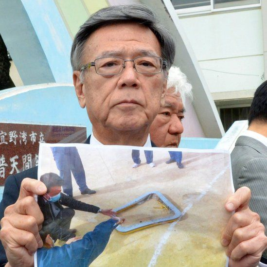 Okinawa Governor Takeshi Onaga shows a picture of the window that fell from the helicopter