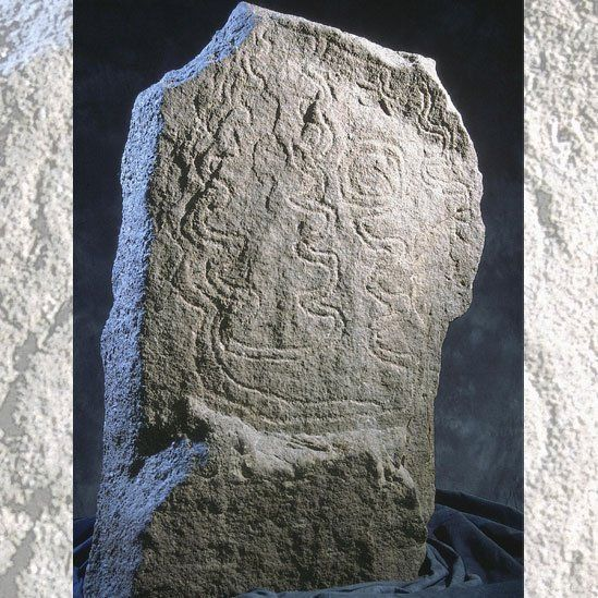 Standing stone decorated with carved zig-zag patterns on its surface