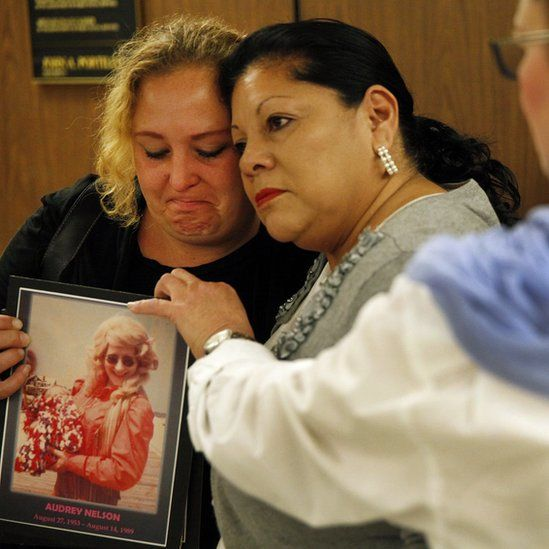 Loved ones of two of his victims embrace at 2014 trial, holding an image.