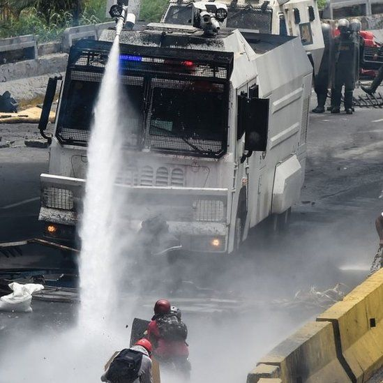 Opposition activists face a police water cannon during a protest against Venezuelan President Nicolas Maduro in Caracas (03 May 2017)