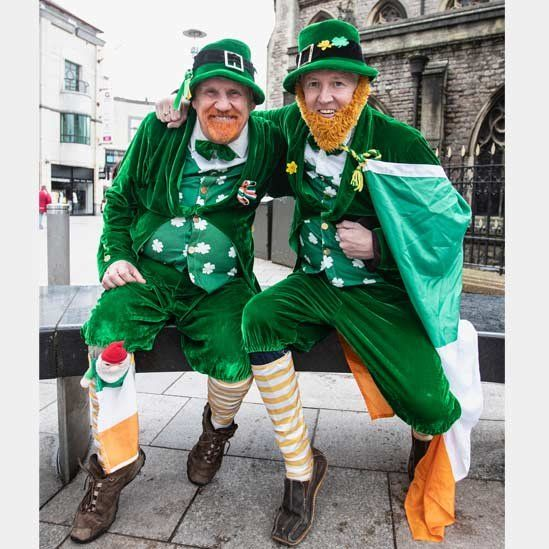Two men dressed in green costumes with fake ginger beards