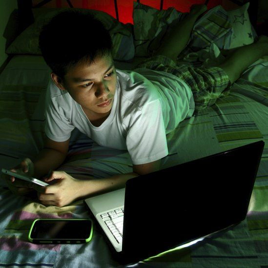 Boy using devices at night