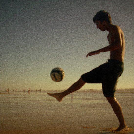 A young man plays football on a beach