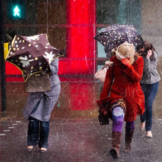 Women carrying umbrellas crossing the street