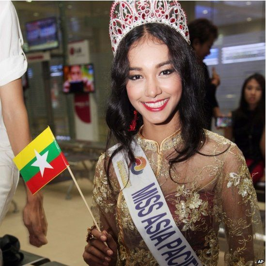 In this 5 June 2014 file photo, Myanmar model May Myat Noe, winner of Miss Asia Pacific World 2014 pageant, waves a miniature flag of the country upon her arrival at Yangon International Airport in Yangon, Myanmar.