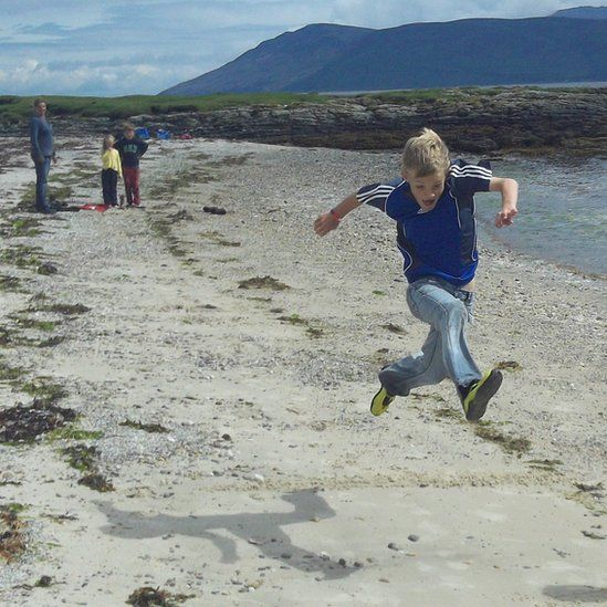 Finlay runs and jumps on the beach