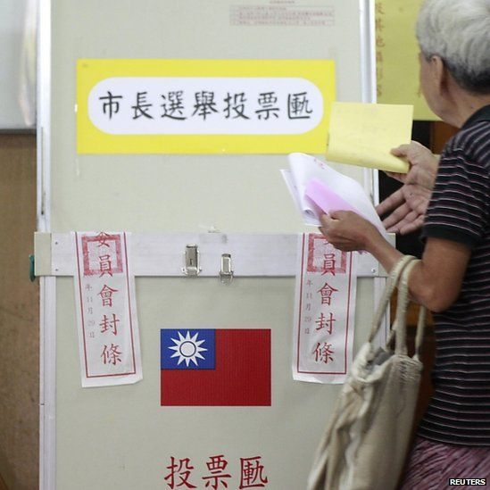 A woman casts her ballot at a voting station during local elections in Taipei. Photo: 29 November 2014