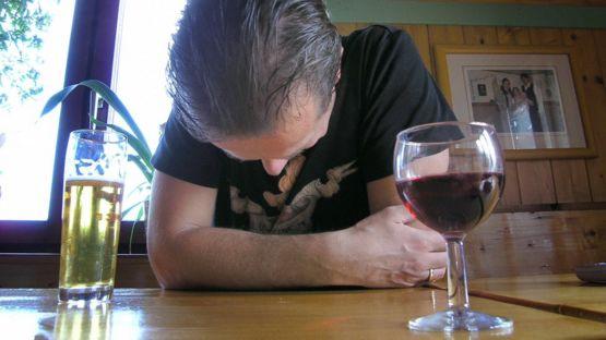 Hombre en una barra de bar con vino y cerveza