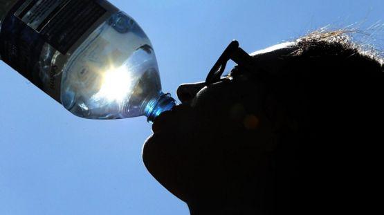 man drinking water in sun